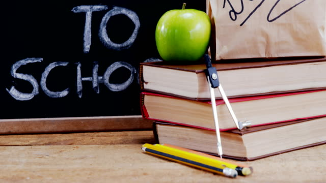 Apple and book with school supplies on table video