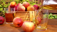 Apple juice and a basket of ripe apples on a wooden table video