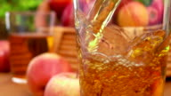 Apple juice apple juice is poured into a glass and basket apples video