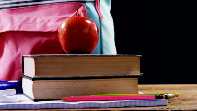 Apple on book stack with schoolbag video