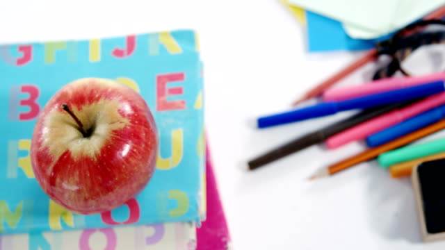 Apple on stack of books with various stationery video