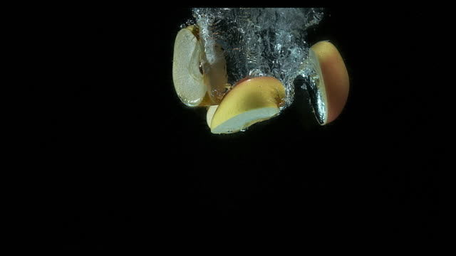 Apples, malus domestica, Fruit entering Water against Black Background, Slow Motion 4K video