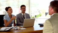 Applicant having a job interview in front of business people video