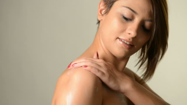 Applying skin cream to a bare shoulder video