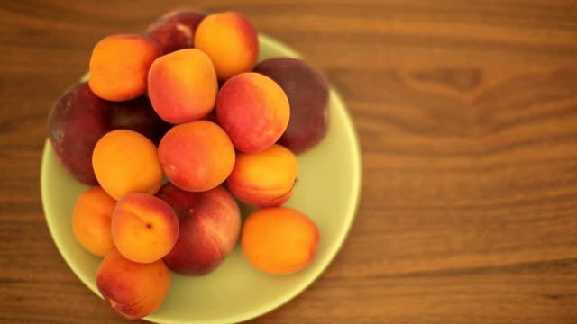 Apricots and peaches in a bowl on a wooden table video