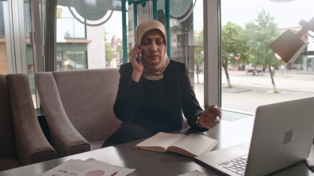 Arab businesswoman making phone call in cafe video