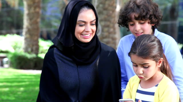 Arab family enjoying with smartphone at park video