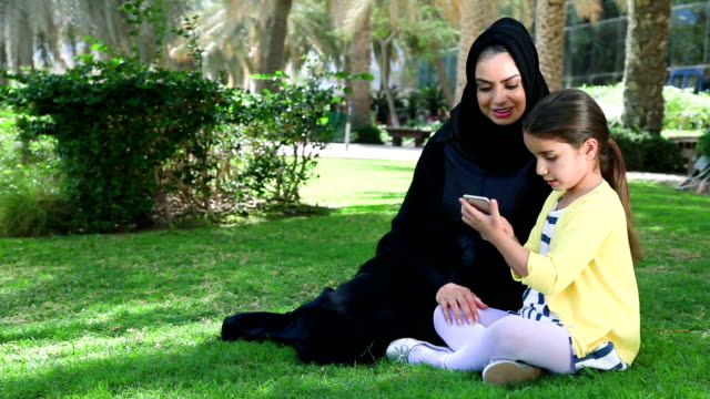 Arab mother and daughter enjoying with smartphone at park video