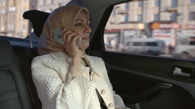 Arab woman answering  phone in backseat of car video