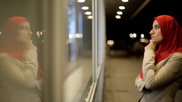 Arab woman watches on  shop window video