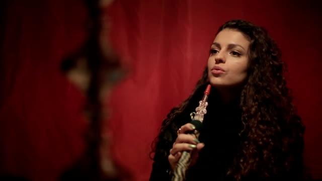 Arabian woman smoking shisha or hookah. Close up. video