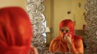 Arabic Woman in Orange Hijab Applies Eyeliner video