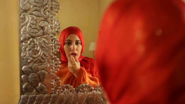 Arabic Woman in Orange Hjiab Applies Lipstick video