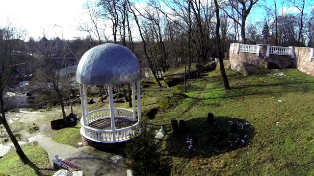 Arbor in park with small river. Aerial video