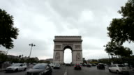 Arc De Triomphe on a cloudy day. Long shot, centered. Tilt from the sky to the Arc and to the ground. Some traffic drives through. video
