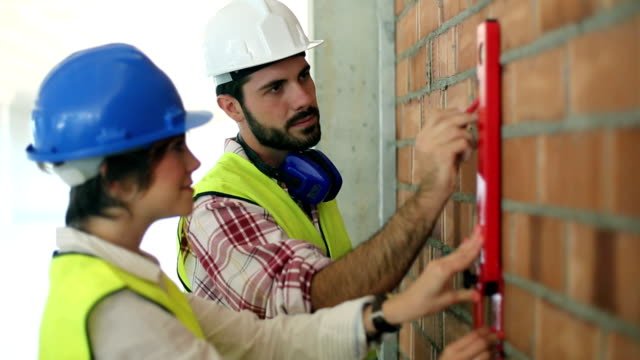 Architect and builder marking a wall at the construction site video