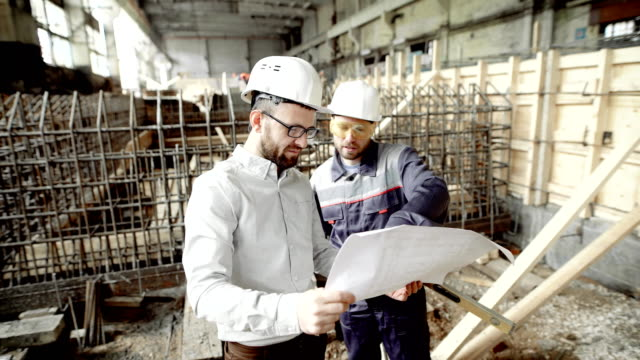 Architect and chief foreman at the construction site of the plant. Men discuss drawbacks in the drawing. Against the background of construction work video