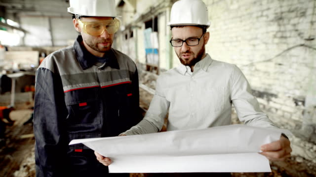 Architect and worker at the construction site of the plant. The chief architect looks through the drawing and decides on further work video