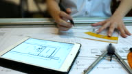 Architect drawing and comparing a blue print structure with digital tablet, 4K(UHD) video