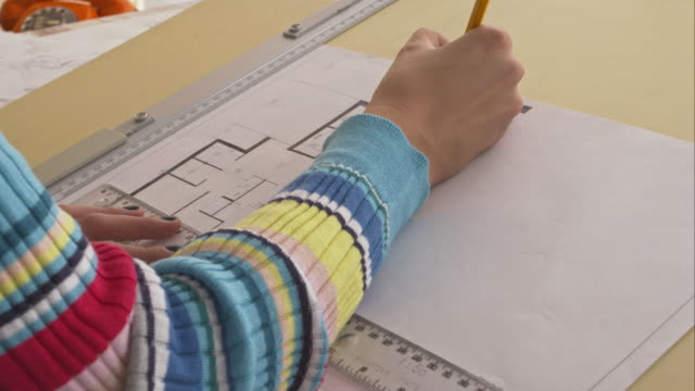 Architect drawing blueprint in office, close-up video