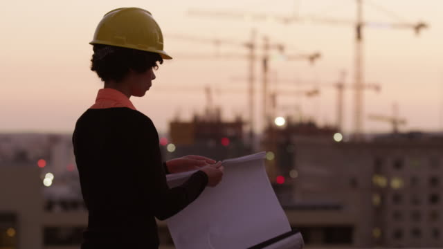 Architect holding plans looking at construction site at sunset video
