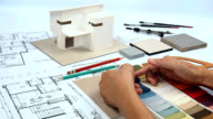 Architect & interior designer working at worktable with home model, blue print, fabric swatch video