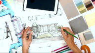 Architect & interior designer working at worktable with tablet, blue print video
