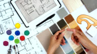 Architect & interior designer working at worktable withfabric swatch, tablet, blue print video