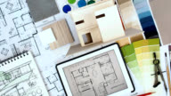 Architect & interior designer worktable with home model, tablet, blue print video