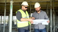 Architect talking with contruction manager about building project. Slider shot. video