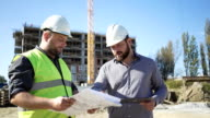 Architect talkng with contruction manager. video