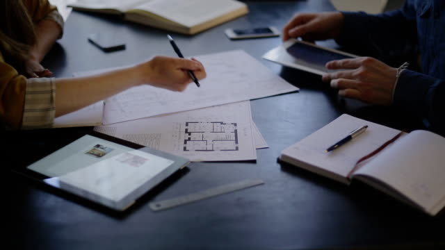 Architect woman and her client is a man sitting at the table and discuss the blueprint video