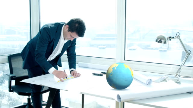 Architect works in front of the planet earth - 4K video