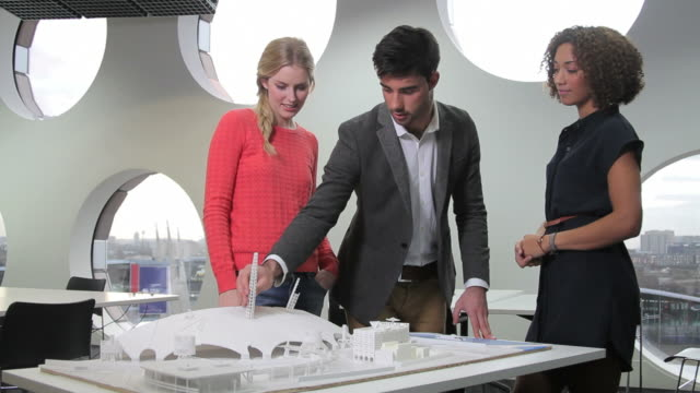 Architects giving presentation and studying maquette video
