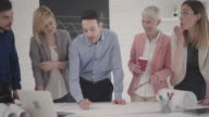 Architects reviewing blueprints in the office. video