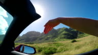 SLOW MOTION: Arm outside of convertible car playing with wind against sunny sky video