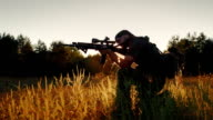 Armed men in camouflage. It takes aim at the optical sight. On the Sunset video