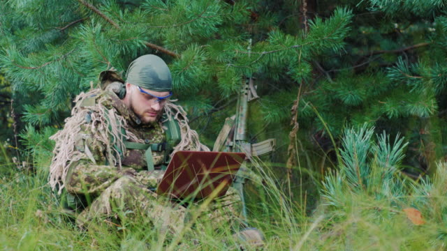 Armed men in camouflage sitting in the bush, uses a laptop video