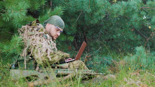 Armed men in camouflage sitting in the woods. It uses laptop. Side view video