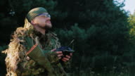 Armed men in camouflage uses a remote control. looking up video