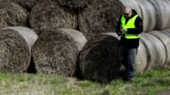armer with tablet PC numbering the hay bales video