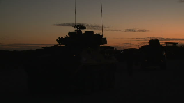 Army trucks on dusk moving out to patrol video