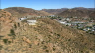around rocky ridge to reveal springbok - Aerial View - Northern Cape,  Namakwa District Municipality,  Nama Khoi,  South Africa video