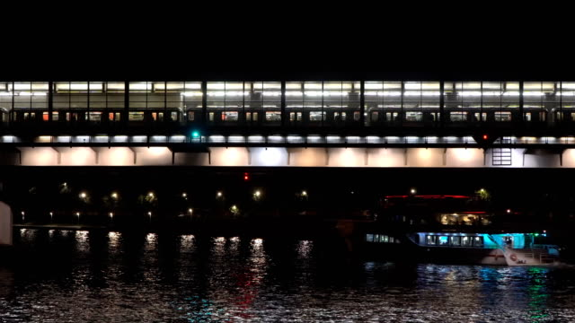 arrival and departure of subway train on the station located on the bridge over the river video