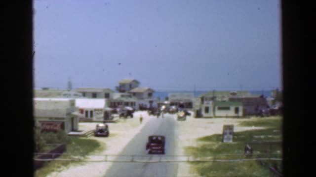 1952: Arrival oceanside beach quaint small town postwar village. video