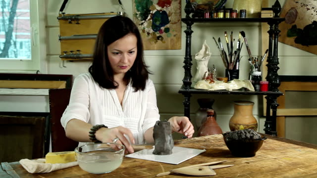 Artisan woman shaping clay sculpture video
