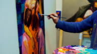 artist brush mix color oil painting on palette is holding in his hand closeup video