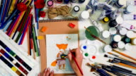 Artist desk from above. Hands drawing using watercolors, art tools. Top view video