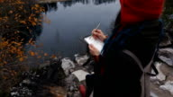 artist girl painting sitting on the rocks at the cliff, notepad. Wonderful fall view video
