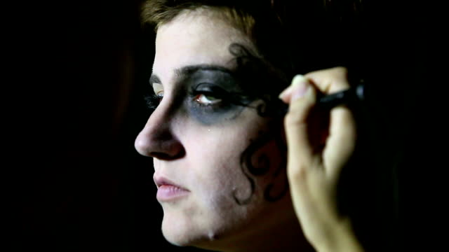 Artist hand painting woman's face for Halloween video